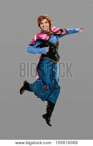 Beautiful young woman dressed in vintage costume jumping isolated over gray background