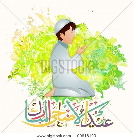 Cute Muslim boy praying Namaz (Islamic Prayer) and colorful Arabic calligraphy of text Eid-Ul-Adha Mubarak on floral design decorated green color splash background.