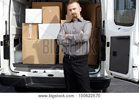Young delivery man near truck with packages. Parcel service.