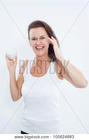 Brunette Woman Applying Eye Cream To Face