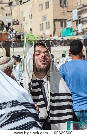 JERUSALEM, ISRAEL - OCTOBER 12, 2014: The area in front of Western Wall of  Temple filled with people.  Morning autumn Sukkot. The young guy in tallit prays