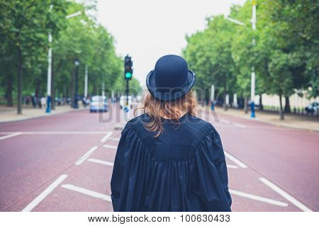 Woman In Hat And Graduation Gown In The Street