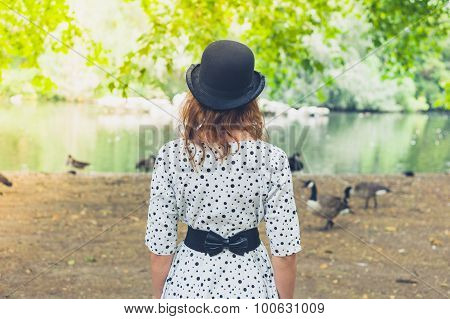 Woman In Bowler Hat By Pond In Park