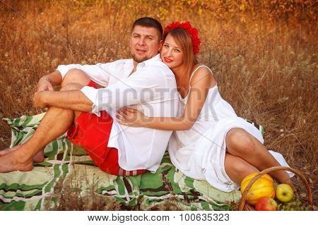 Husband And Wife Are Sitting On The Plaid In The Park
