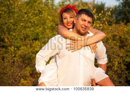 Woman On The Shoulders Of Men. A Couple On A Walk In The Park