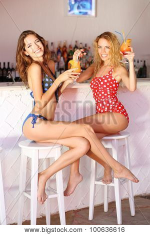 Two young girls enjoying cocktails in beach bar