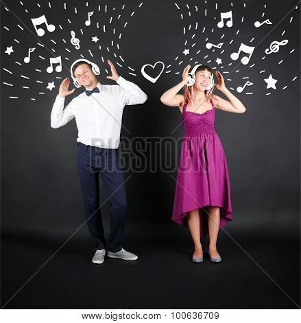 Funny young couple with headphones, on black background