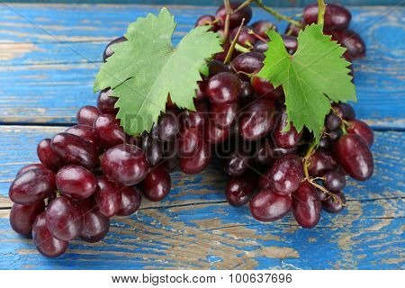 Fresh ripe grapes on old wooden table