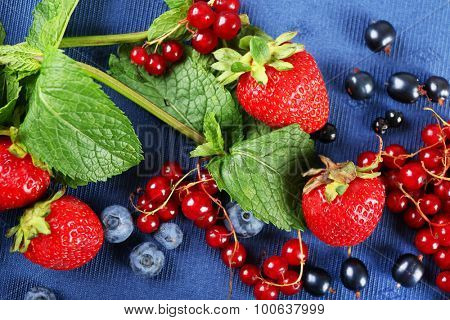 Group of fresh summer berries with mint on blue tablecloth, closeup
