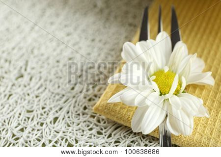 Fork with beautiful flower on table close up