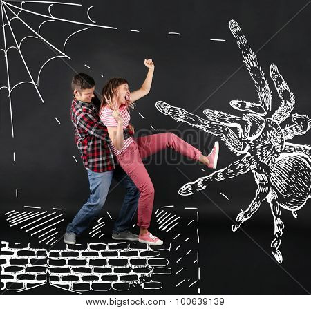 Funny young couple fighting with a big spider, on black background