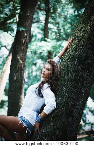 beautiful young woman in white shirt and jeans shorts lean on tree in park, look at camera, natural light