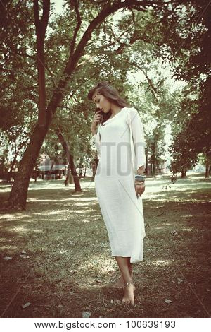 beautiful young barefoot woman in long linen white dress stand standing between trees full body shot, natural light