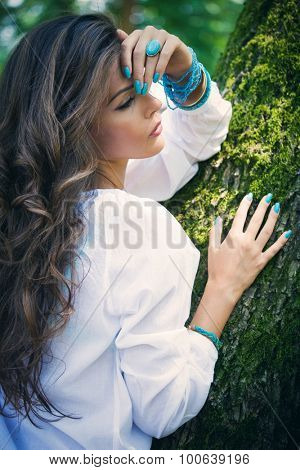 young woman portrait wearing white shirt and turquoise nail polish, ring and bracelets, lean on tree, day shot, natural light, side view