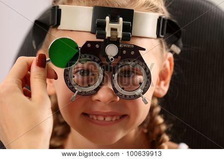 Young girl undergoing eye test with Spectacles on blurred background