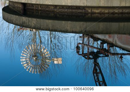 Old windmill reflected in a water basin at the Landschaftspark Duisburg-Nord a public park in the German city of Duisburg. The centerpiece of the park is formed by the ruins of a blast furnace complex shut down in 1985.