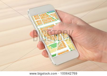 Hand holding smart mobile phone with map gps navigation application on wooden background