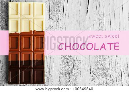 Bar of chocolate on color wooden surface and space for your text