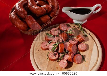 still life sliced sausages on a plate with rosemary, pepper and sauce