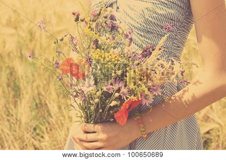 Woman holding beautiful bouquet of wildflowers outdoors