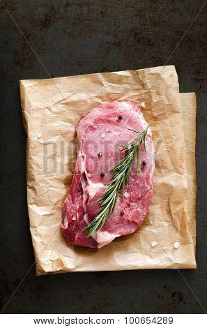 Raw steak beef ribeye on brown paper against dark background, overhead perspective