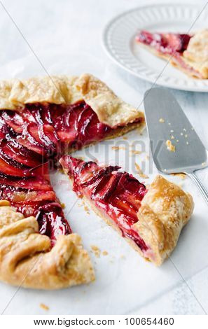 Rustic fruit plum tart galette pie cut into slices with crumbs on baking wax paper