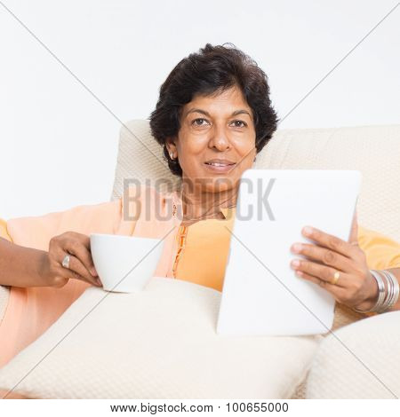 Portrait of a 50s Indian mature woman using tablet computer at home. Older people, modern technology concept. Indoor senior people living lifestyle.