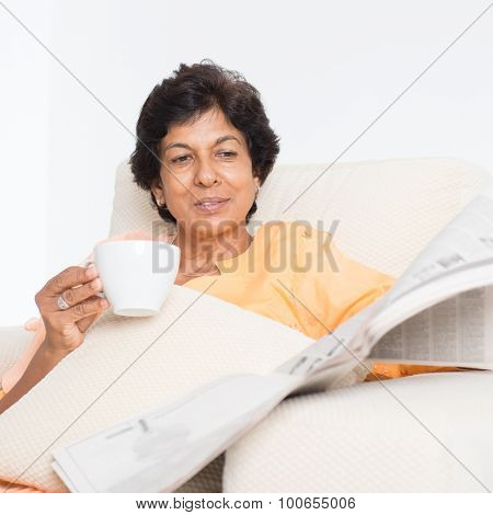 Portrait of a 50s Indian mature woman reading newspaper and drinking coffee at home. Indoor senior people living lifestyle.