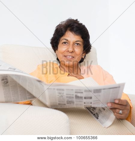 Portrait of a 50s Indian mature woman reading newspaper at home. Indoor senior people living lifestyle.