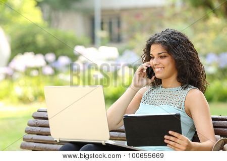 Entrepreneur Working With Multiple Devices In A Park