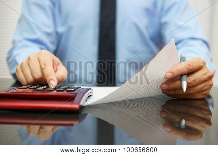 Businessman Reading  Document With Numbers And Calculating