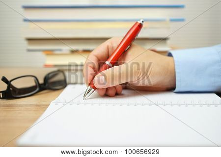 Student Hand Is Writing In Notepad With Bunch Of Book In Background