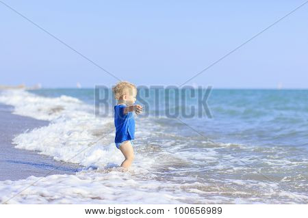 baby playing on the waves of the sea