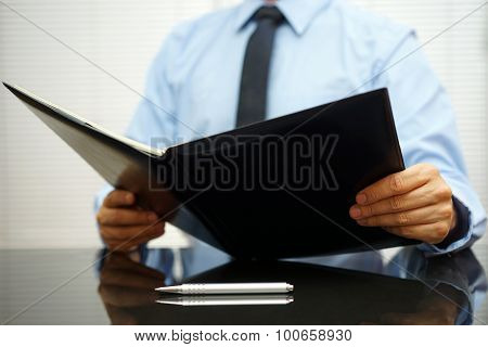 Businessman Is Reading Report From Notebook