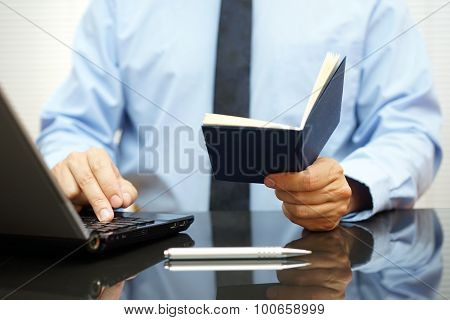Bussinessman Is Reading Informations From Notebook And Typing On Laptop Keyboard