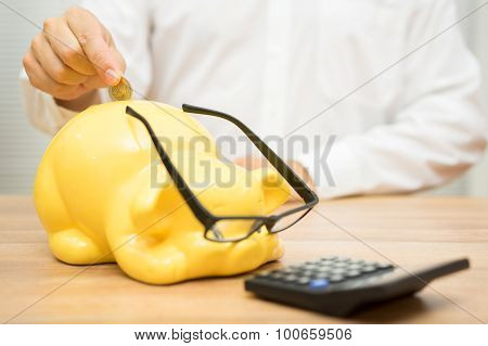 Man Putting Coin In Piggy Bank Who Looks In Calculator, Concept If Savings And Safe Investing
