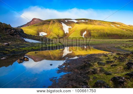 Light golden dawn illuminates the mountains and glaciers national park Landmannalaugar. The  sunrise in Iceland