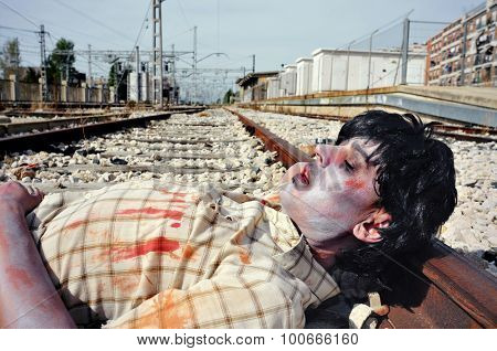 closeup of a scary zombie man lying down at the railroad tracks