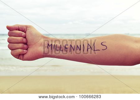 closeup of a young man with the word millennials written in his arm in front of the sea