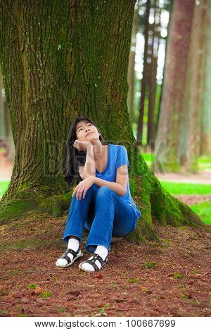 Young Teen Girl Sitting Under Large Pine Trees, Thinking