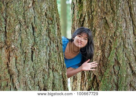 Teen Girl Peeking Through Trees, Waving And Smiling