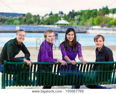 Four Young Multiethnic Friends Together At Beach