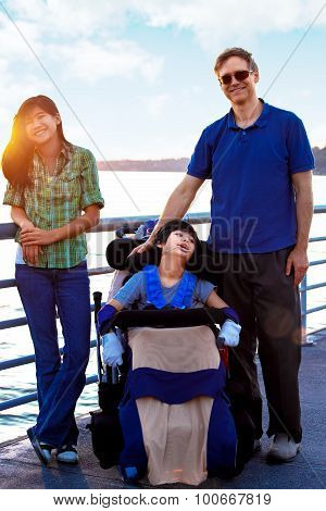 Disabled Child In Wheelchair Outdoors By Lake With Family