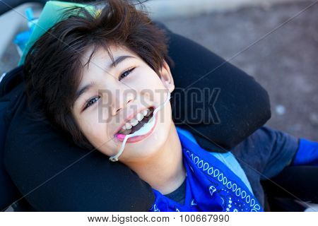 Handsome Little Disabled Boy In Wheelchair, Smiling Up At Camera