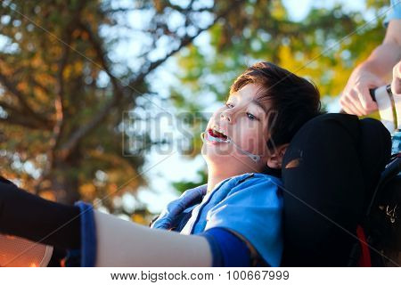 Handsome Little Disabled Boy In Wheelchair, Enjoying Sunset At Park Outdoors