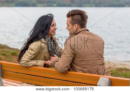 a young, verl liebtes couple sitting on a park bench