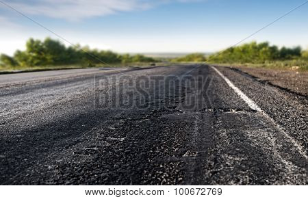 bad asphalt road through the green field and blue sky in summer day