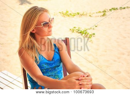 Portrait Of Blonde Sad Girl In Sunglasses Sits On Chair On Sand