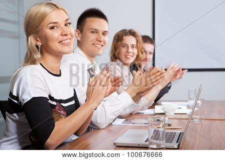 Portrait Of Successful Applauding Young People Sitting In Line
