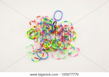 elastic rainbow loom bands on white background.